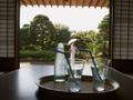 卓上のソーダ水と日傘の女性