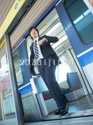 電車から降りるビジネスマン - J...