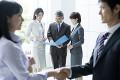 握手をする日本人ビジネスマンとビジネスウーマン