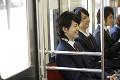 電車に座って会話する男子高校生
