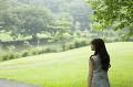 公園で遠くを見つめる若い女性の後ろ姿
