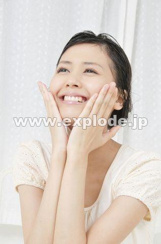 両手で顔をマッサージする若い女性