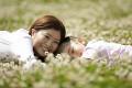 花畑で寝転ぶ母と子