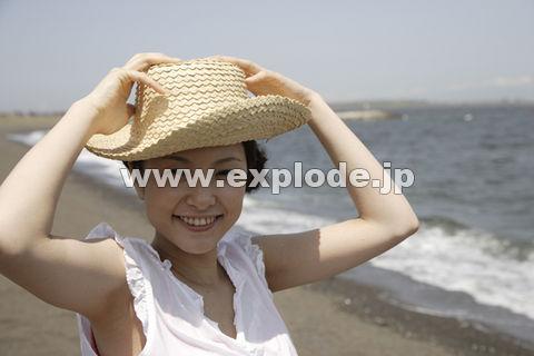 海と麦わら帽子を被った日本人女性