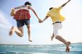 海に向かってジャンプするカップル
