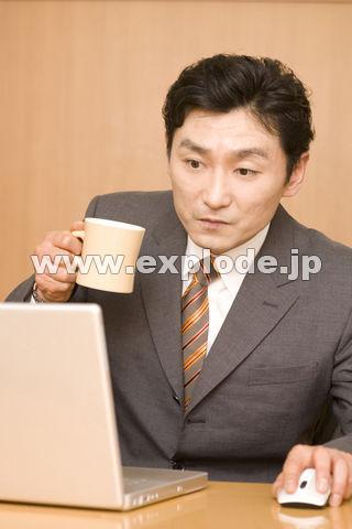 パソコンを見ながらコーヒーを飲むビジネスマン