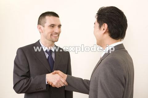 握手する日本人ビジネスマンとアメリカ人ビジネスマン