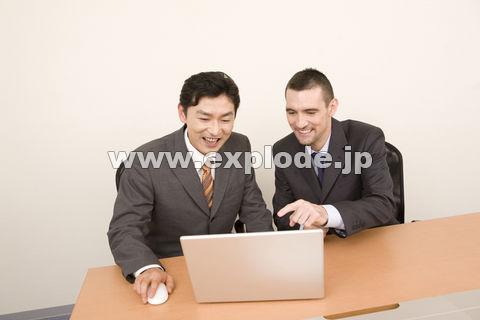 パソコンを見る日本人ビジネスマンとアメリカ人ビジネスマン