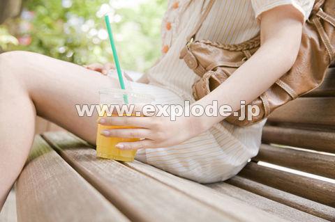 オレンジシュースを片手に持って街中のベンチに座っている女性
