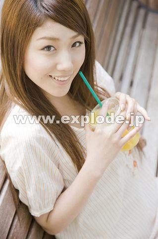 街中のベンチに座りオレンジジュースを飲む女性