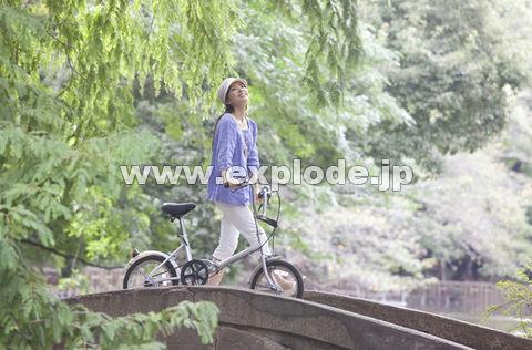 自転車を押しながら橋を渡る女性