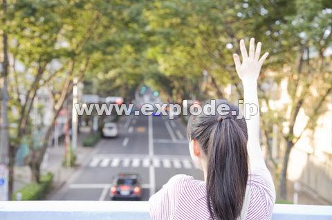 陸橋の上から手を振る女性の後姿
