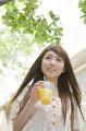 オレンジジュースを持って街中を歩く女性
