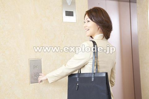 エレベーターのボタンを押すOL