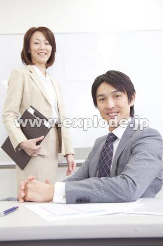 会議室で微笑むビジネスマンとOL