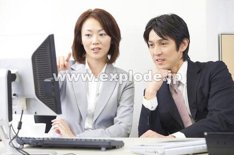 パソコンのモニターを見るOLとビジネスマン