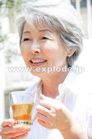 紅茶を飲みながら微笑むシニア女性