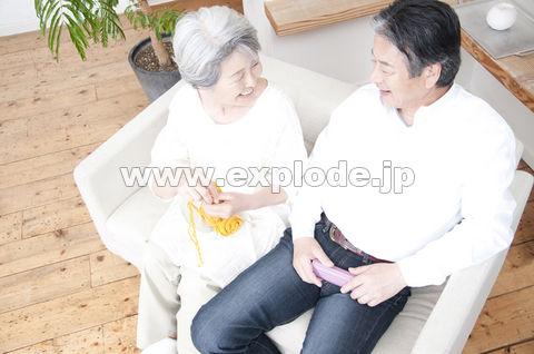 編み物をするシニア女性と笑顔のシニア男性