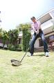 庭でゴルフの練習をするシニア男性