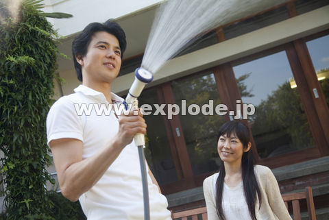 庭に水を撒く男性と見守る女性