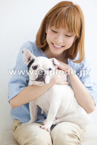 フレンチブルドッグの頭を撫でる笑顔の女性