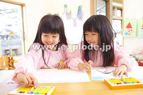 クレヨンで絵を描く幼稚園女児2人