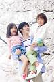 桜の下で子ども二人を抱き上げ微笑む父親