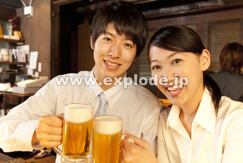 ビールで乾杯するビジネスマンとOL