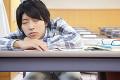 居眠りする男子大学生