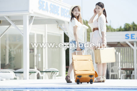 スーツケースを持って振りかえる女性