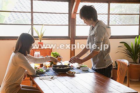 料理を取り分ける男性と座っている女性