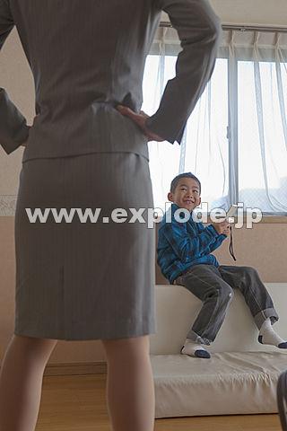 携帯ゲーム機で遊ぶ男の子と仁王立ちの母親