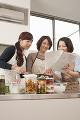 キッチンでレシピを見る三人の女性
