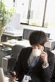 スマートフォンを見てコーヒーを飲む男性