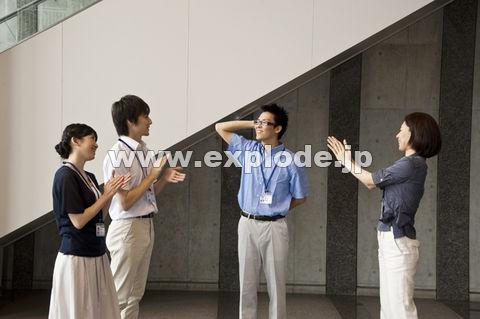 クールビズで照れる男性と拍手する男女3人