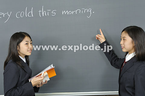 黒板の前に立つ女子高校生二人