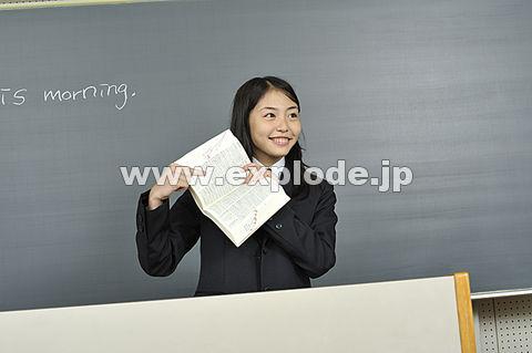 黒板の前で辞書を見せる女子高校生