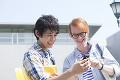 画面を見て笑う留学生と大学生