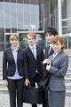 建物の前に立つスーツ姿の男女4人